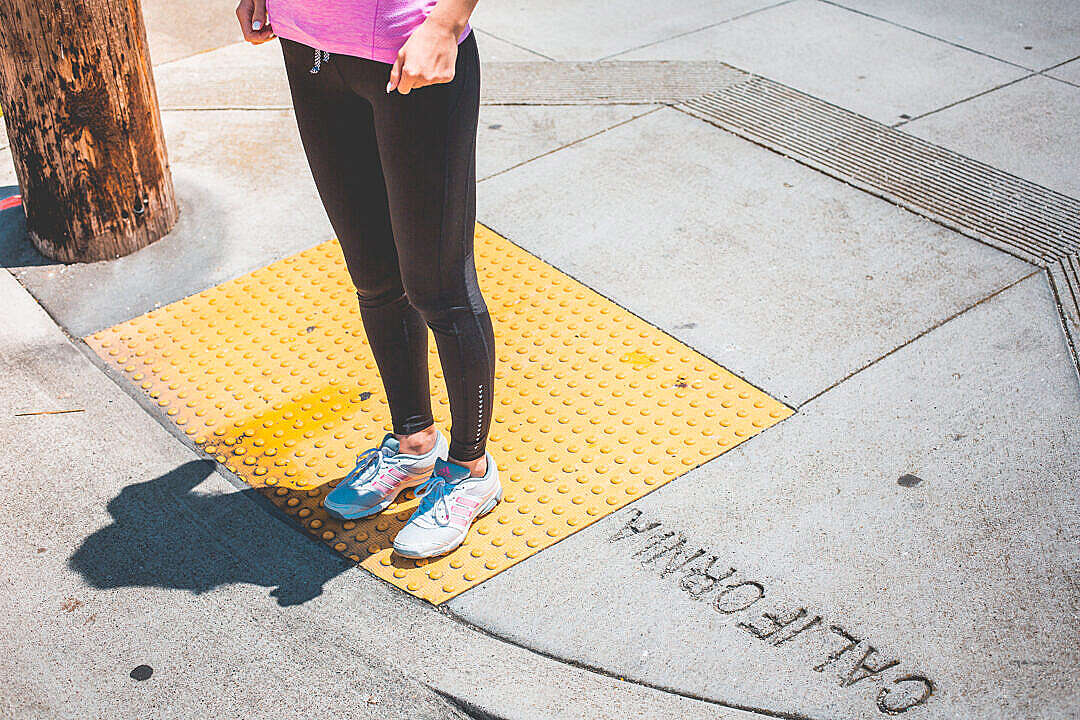 Download Young Female Jogger Waiting at the Edge of a Zebra Crossing FREE Stock Photo
