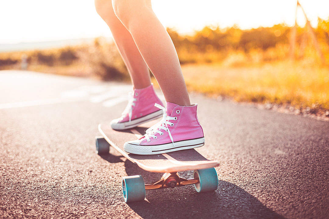 Download Young Girl with Pink Shoes Riding a Longboard FREE Stock Photo
