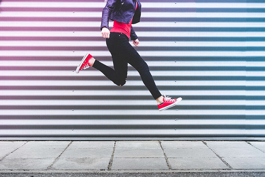 Download Young Happy Woman Jumping in Front of Metal Wall FREE Stock Photo