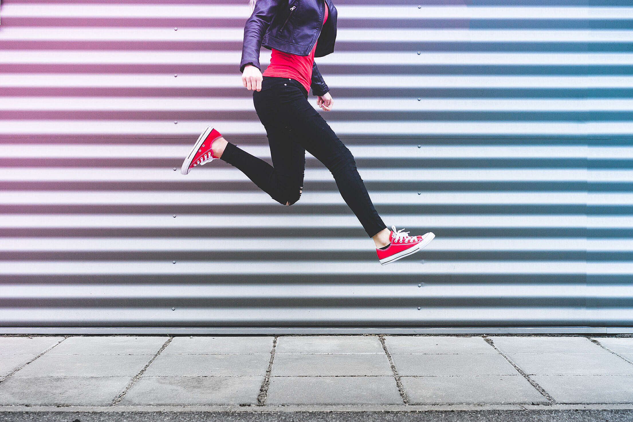 Young Happy Woman Jumping in Front of Metal Wall Free Stock Photo