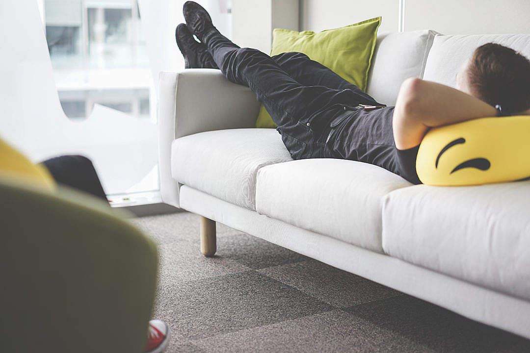 Download Young Man Napping on White Sofa in the Office FREE Stock Photo