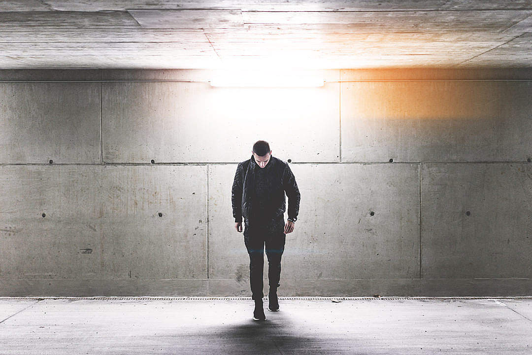 Download Young Man Walking in Conrete Underground Walkway FREE Stock Photo