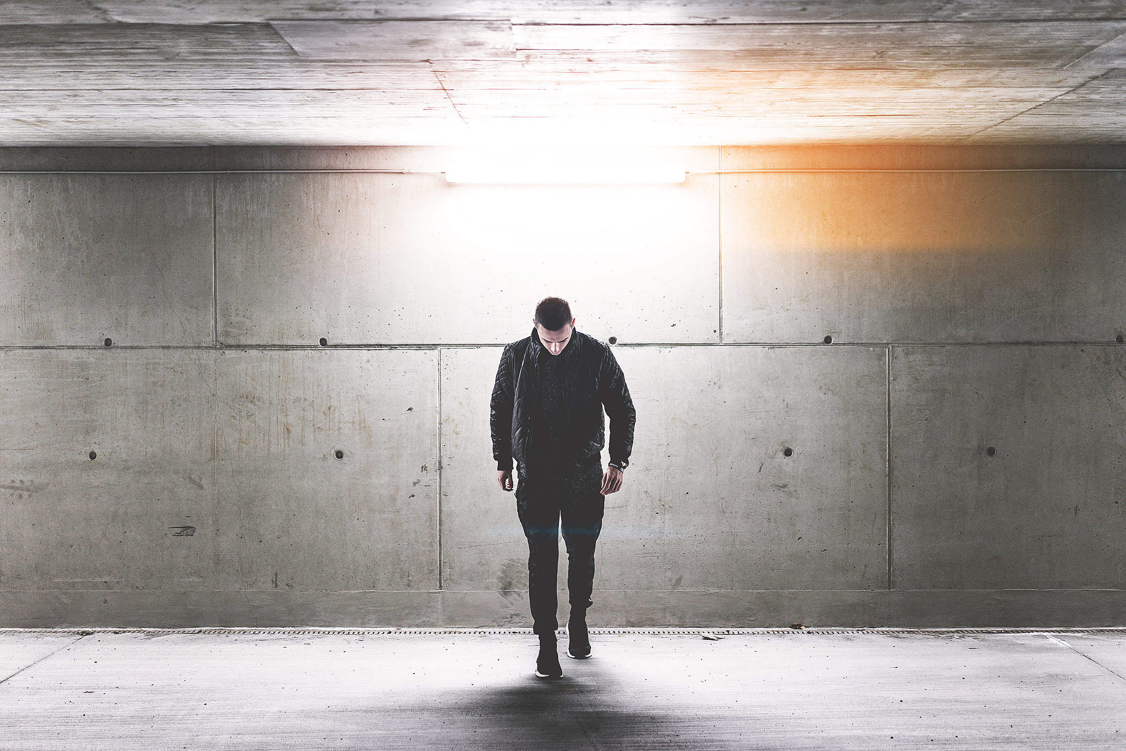 Young Man Walking in Conrete Underground Walkway Free Stock Photo