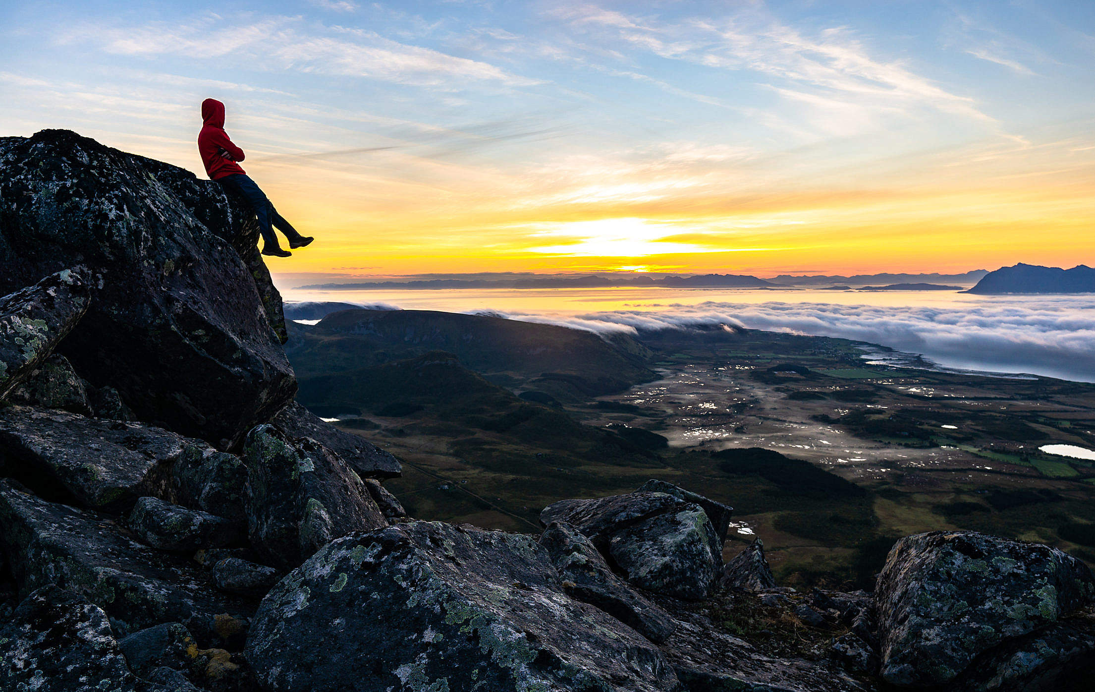 Young Man Watching the Sunrise From Top of the Mountain Free Stock Photo