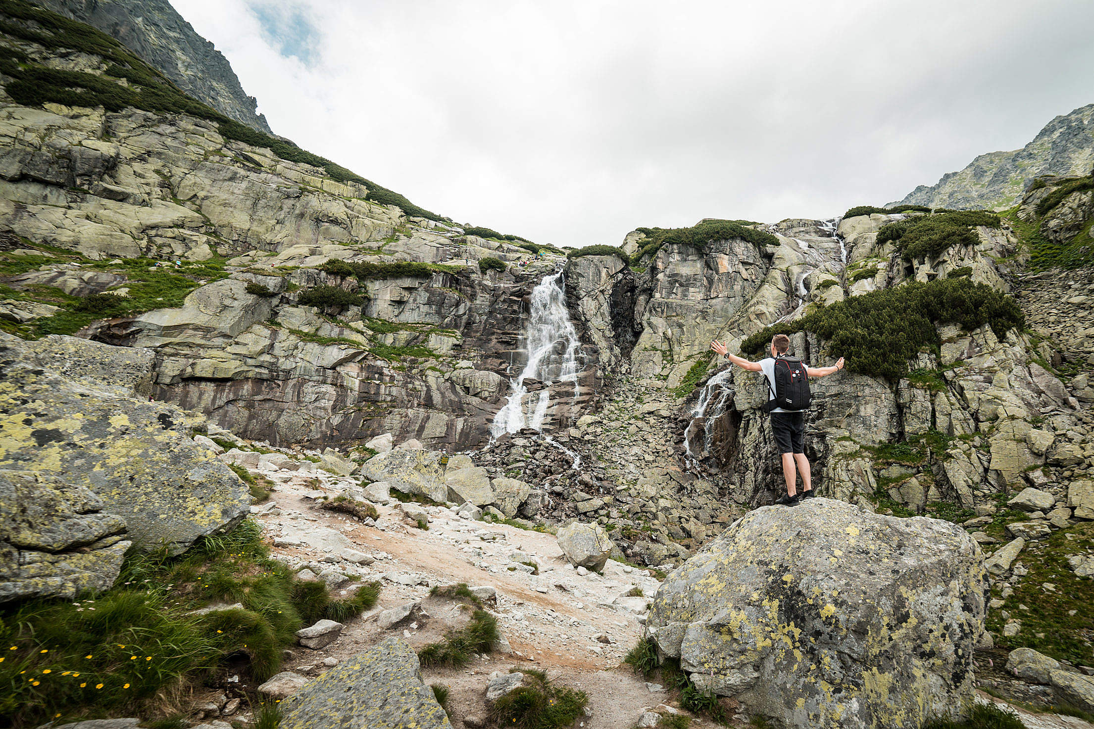 Young Man with Open Arms under Big Waterfall Free Stock Photo
