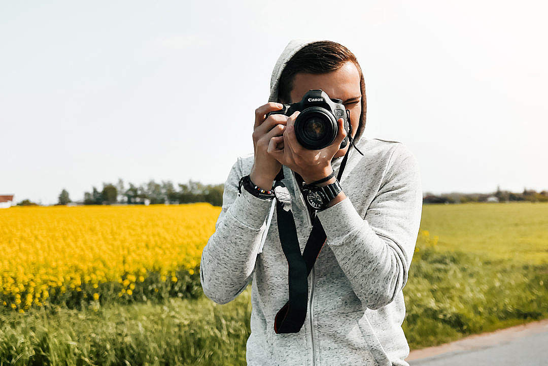 Download Young Photographer in Action Taking a Photo FREE Stock Photo