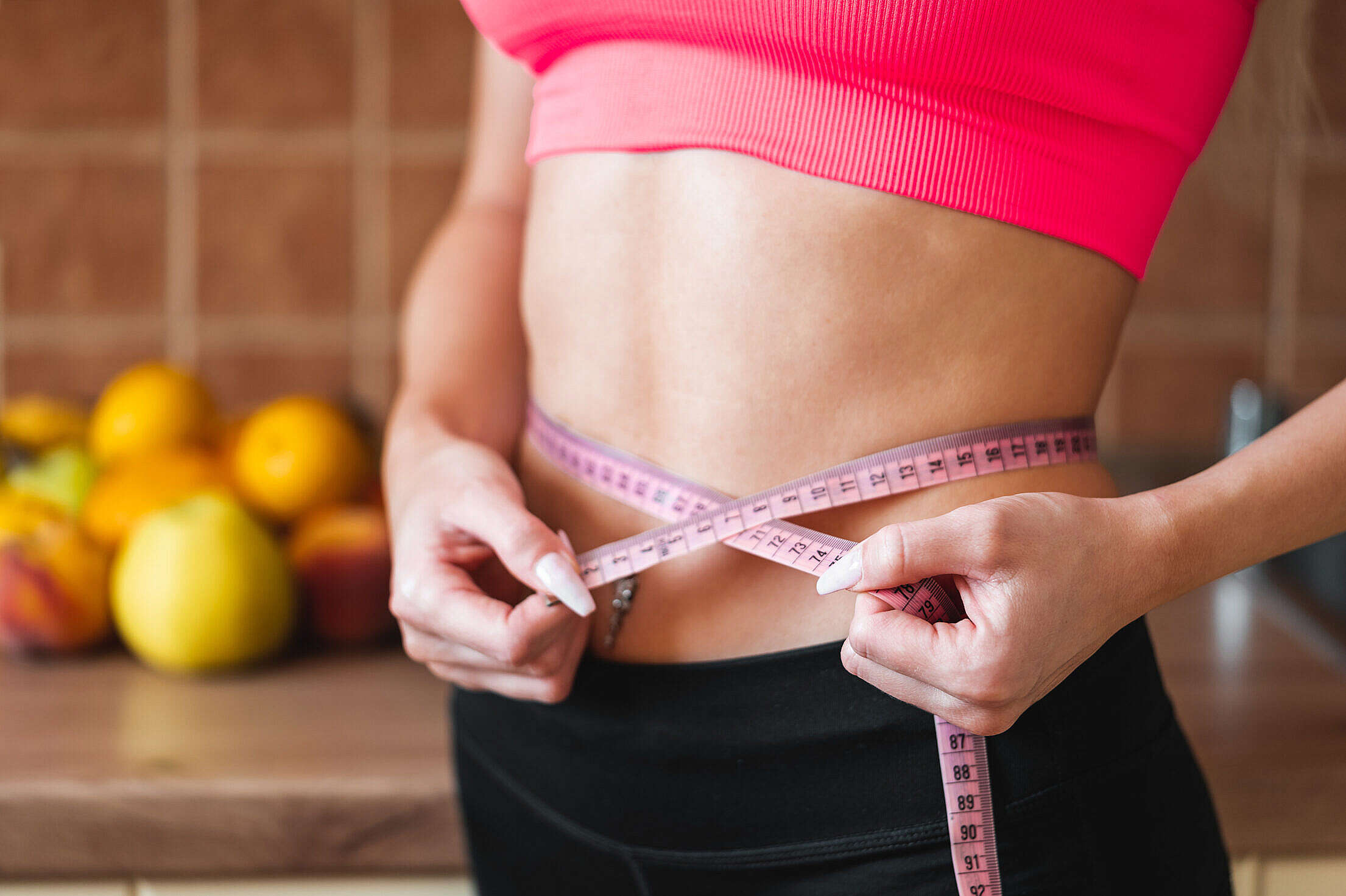 Young Slim Woman Measuring Her Waist by Measure Tape Free Stock Photo