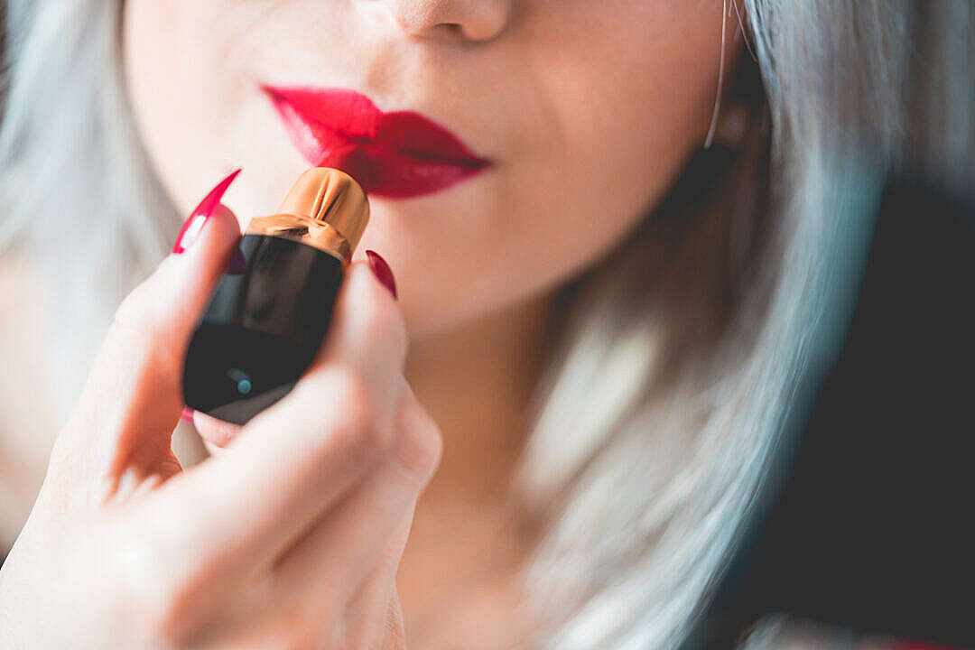 Download Young & Smiling Woman Applying Red Lipstick FREE Stock Photo