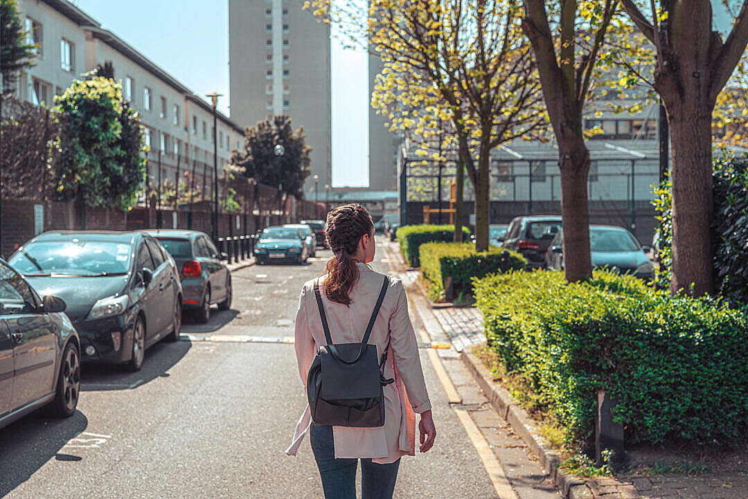 Download Young Solo Traveler Woman Walks Down a Street FREE Stock Photo