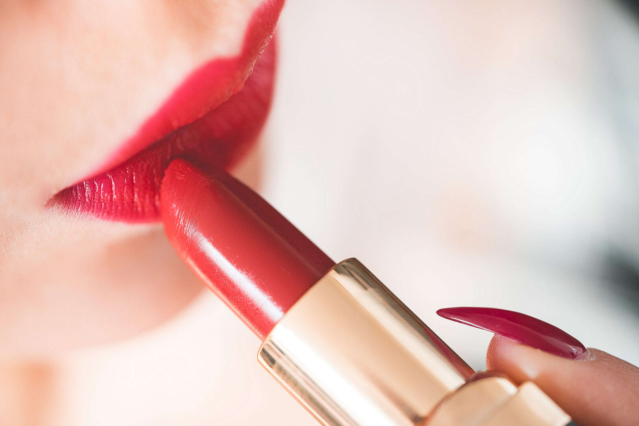 Young Woman Applying Red Lipstick Free Stock Photo