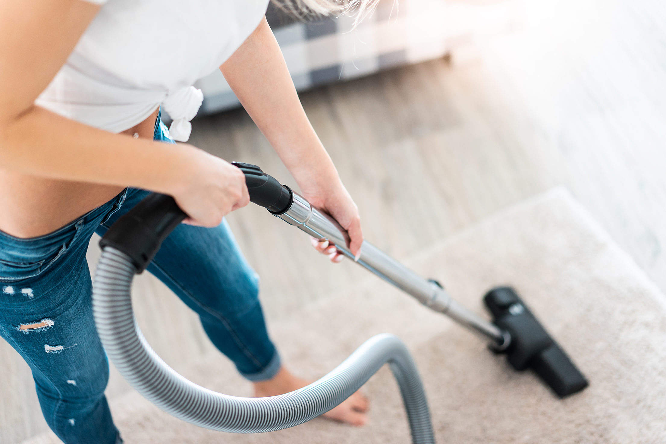 Young Woman Cleaning Carpet with Vacuum Cleaner Free Stock Photo