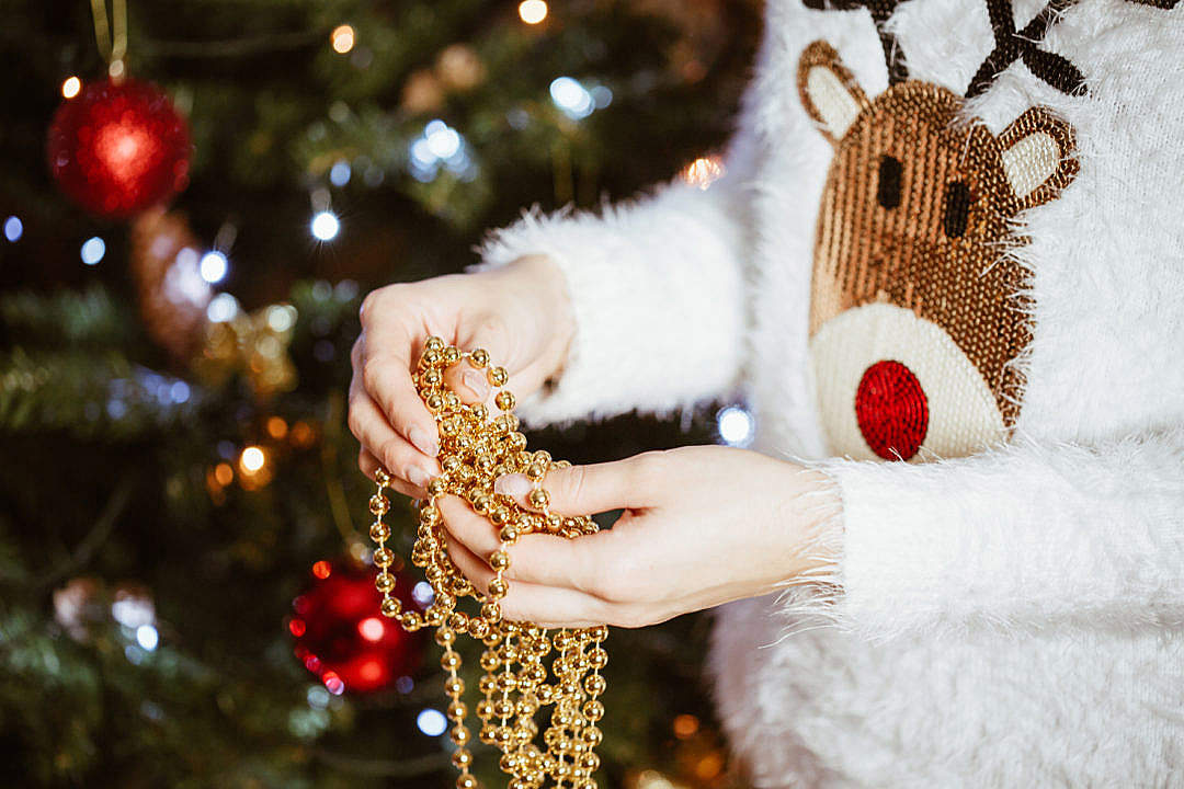 Download Young Woman Decorating Christmas Tree FREE Stock Photo