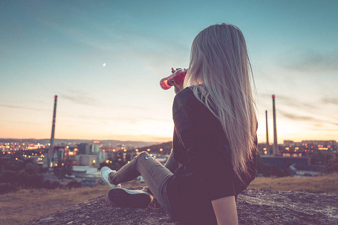 Download Young Woman Drinking Lemonade and Overlooking the City FREE Stock Photo