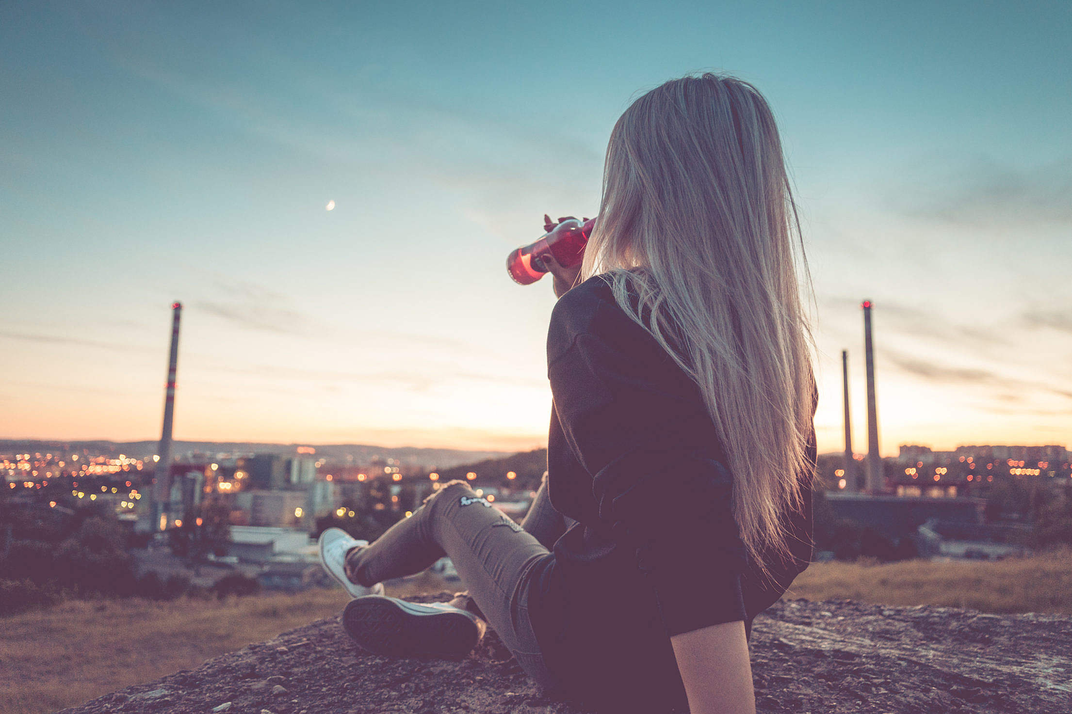 Young Woman Drinking Lemonade and Overlooking the City Free Stock Photo