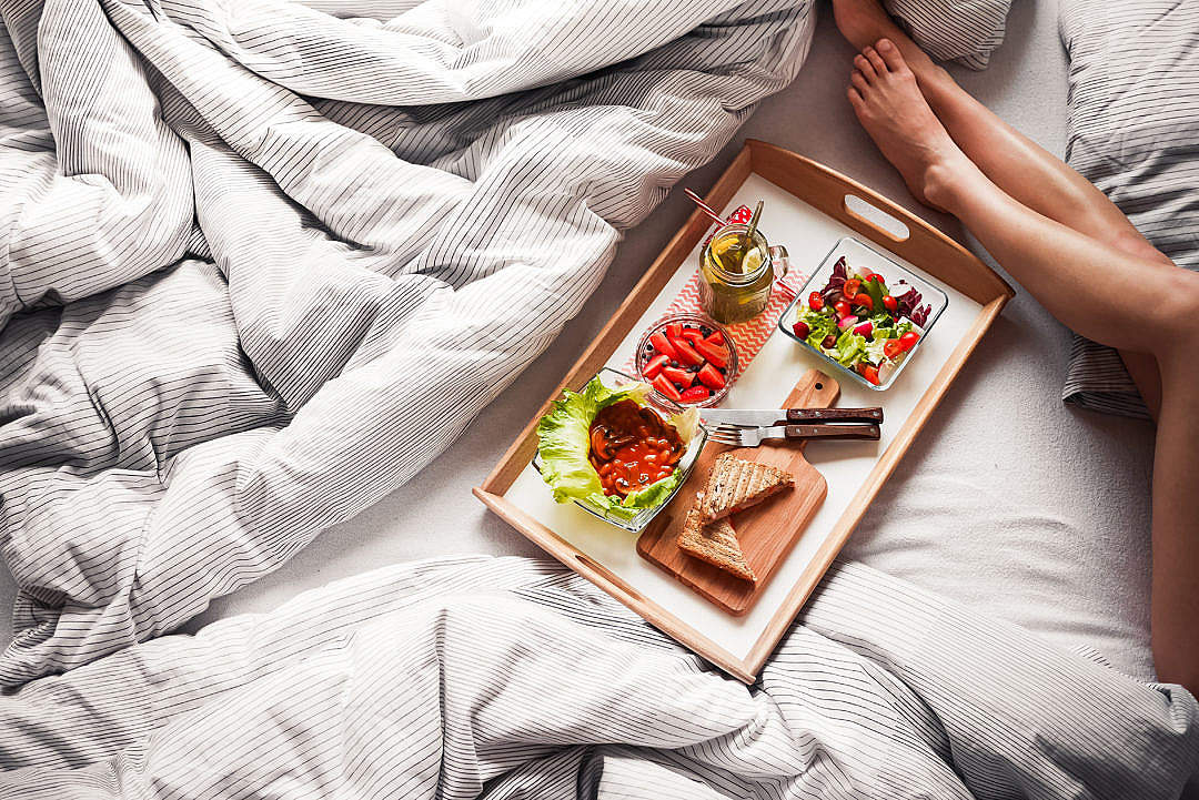 Download Young Woman Enjoying Morning Breakfast in Bed FREE Stock Photo