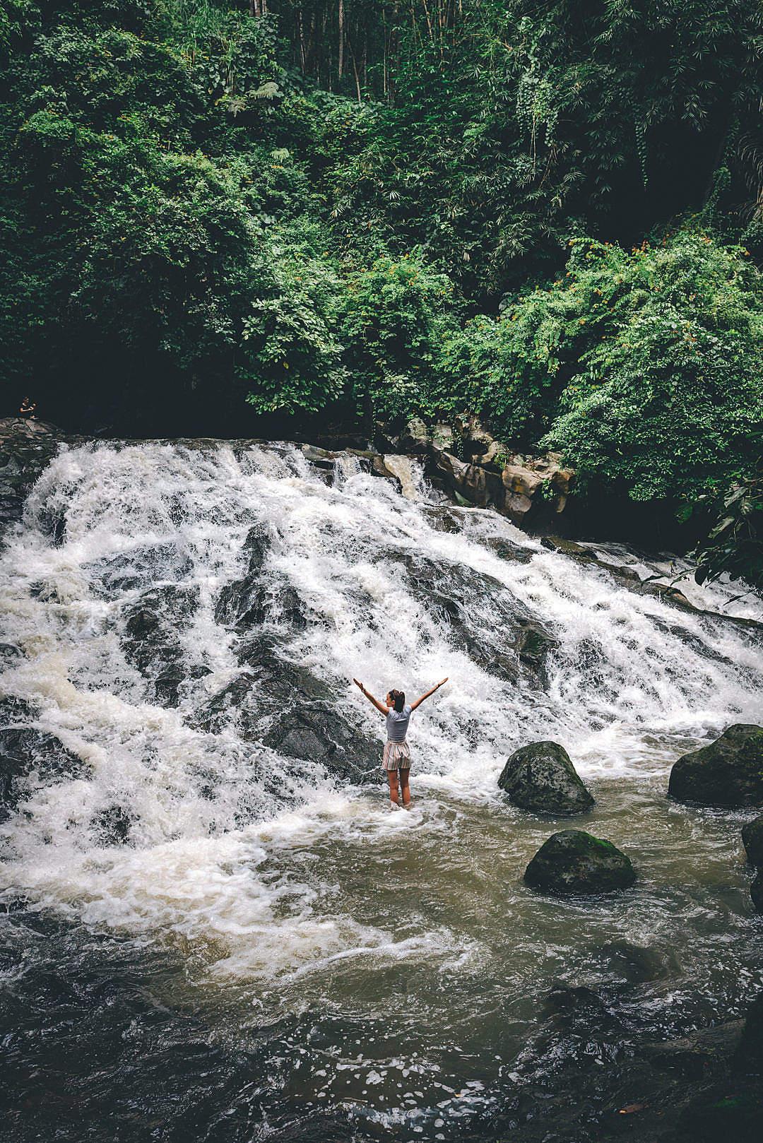 Download Young Woman Enjoying Waterfall in Bali FREE Stock Photo