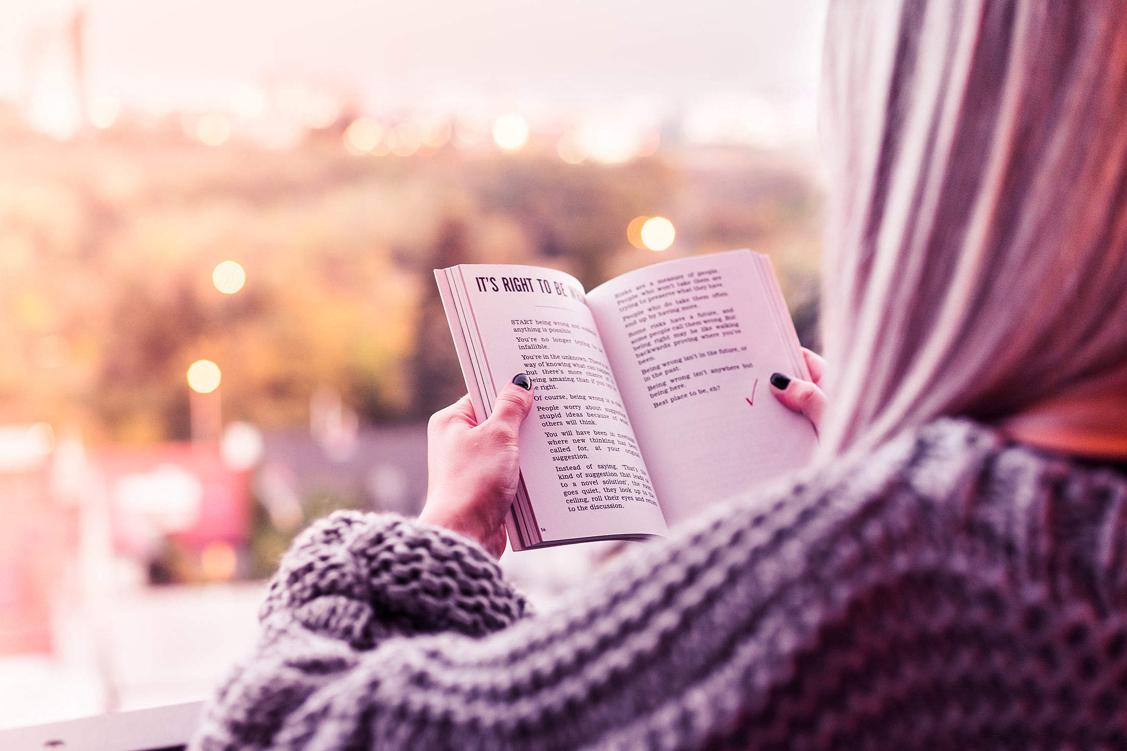 Young Woman Reading a Book on Terrace Free Stock Photo