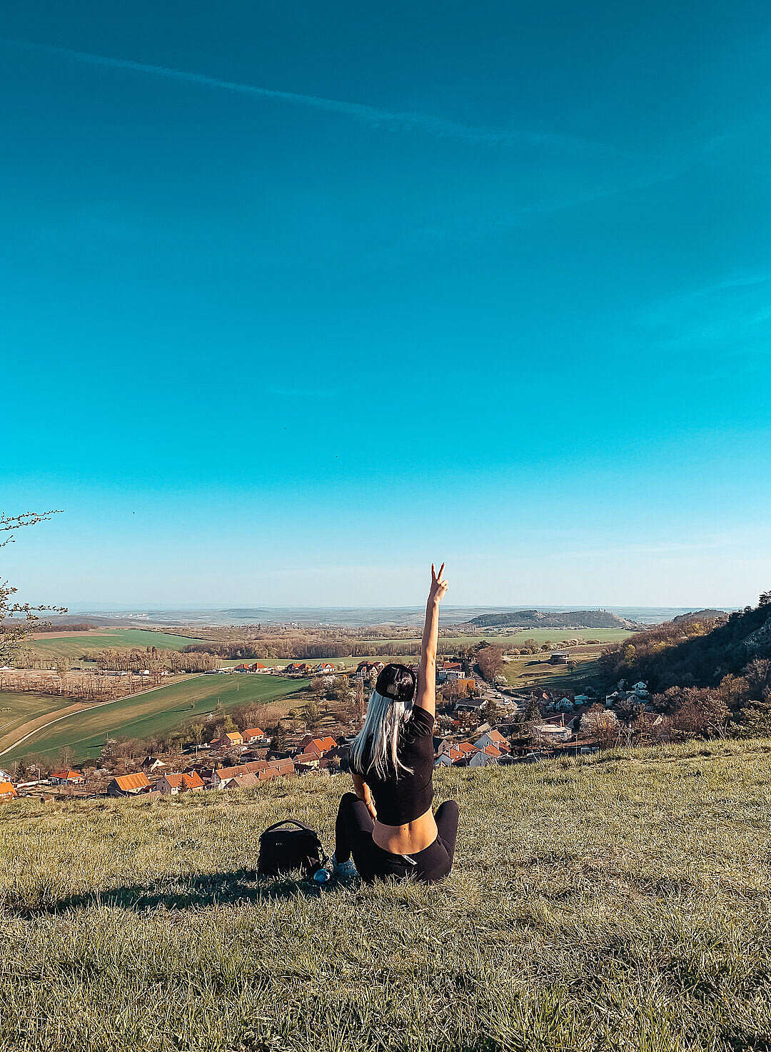 Download Young Woman Sitting on a Hill Showing Peace Sign FREE Stock Photo