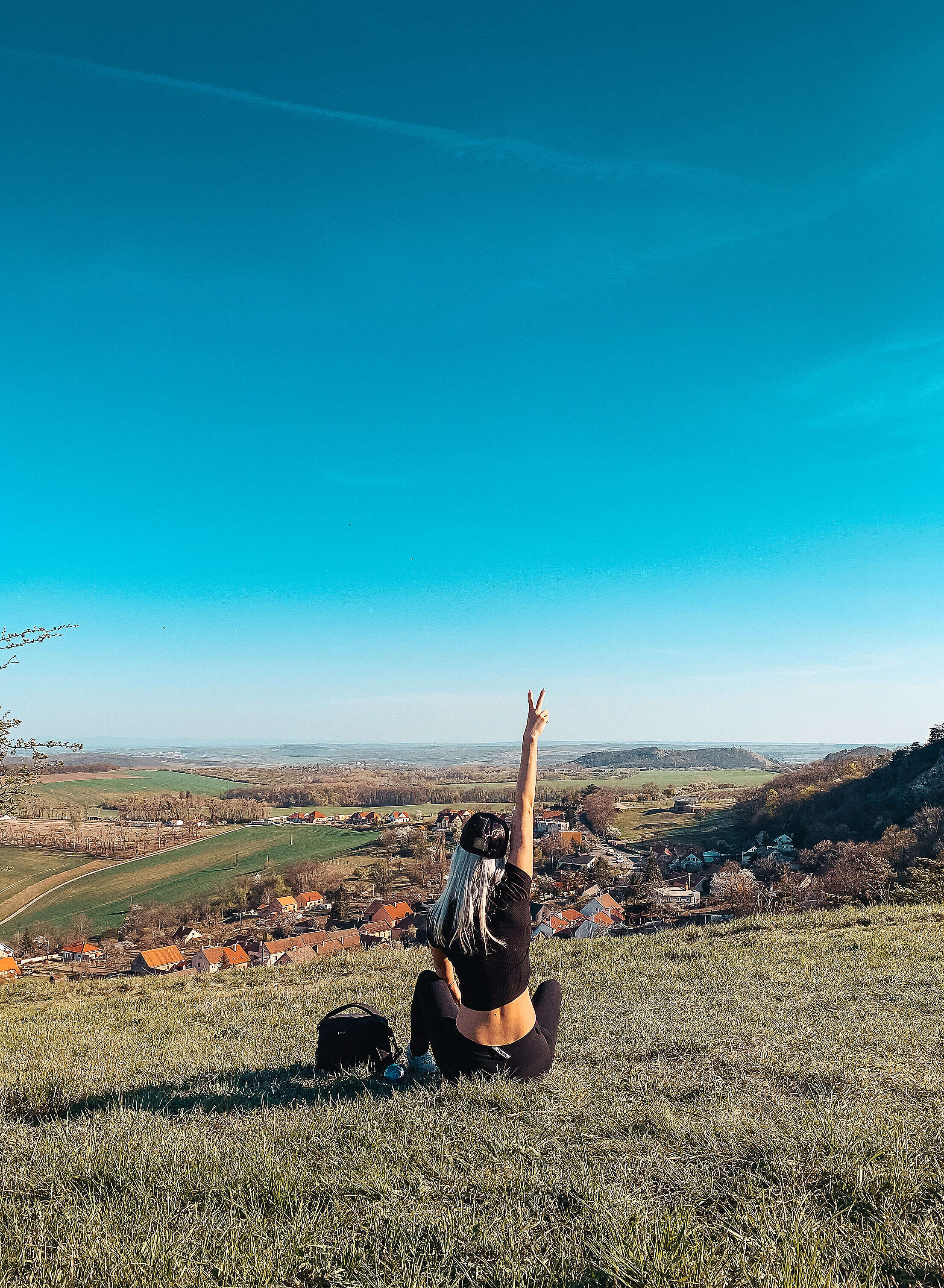 Young Woman Sitting on a Hill Showing Peace Sign Free Stock Photo