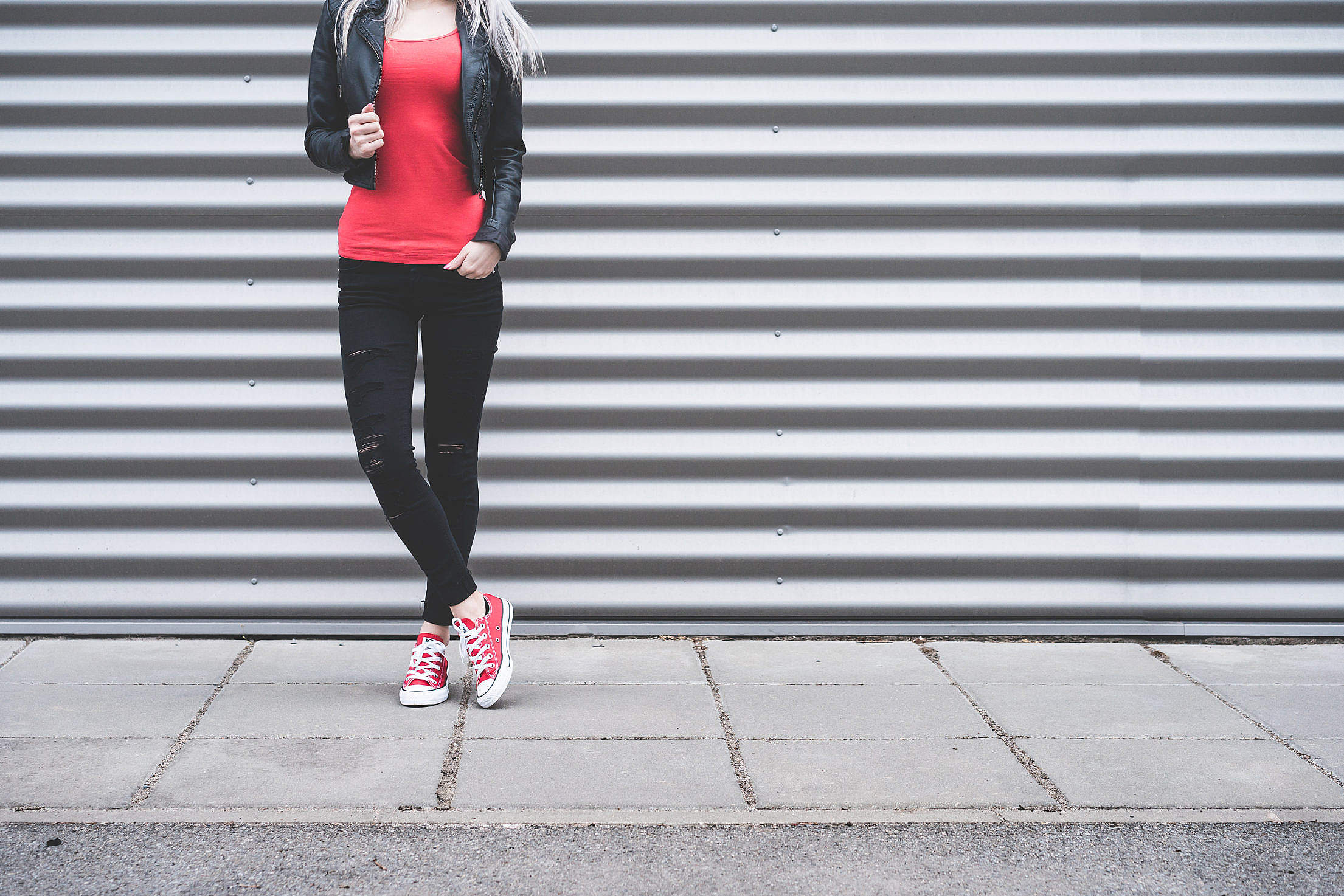 Young Woman Standing in Front of Metallic Wall Free Stock Photo