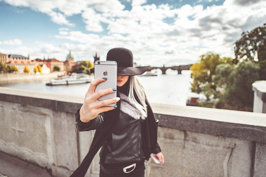 Download Young Woman Taking a Selfie with Her iPhone FREE Stock Photo