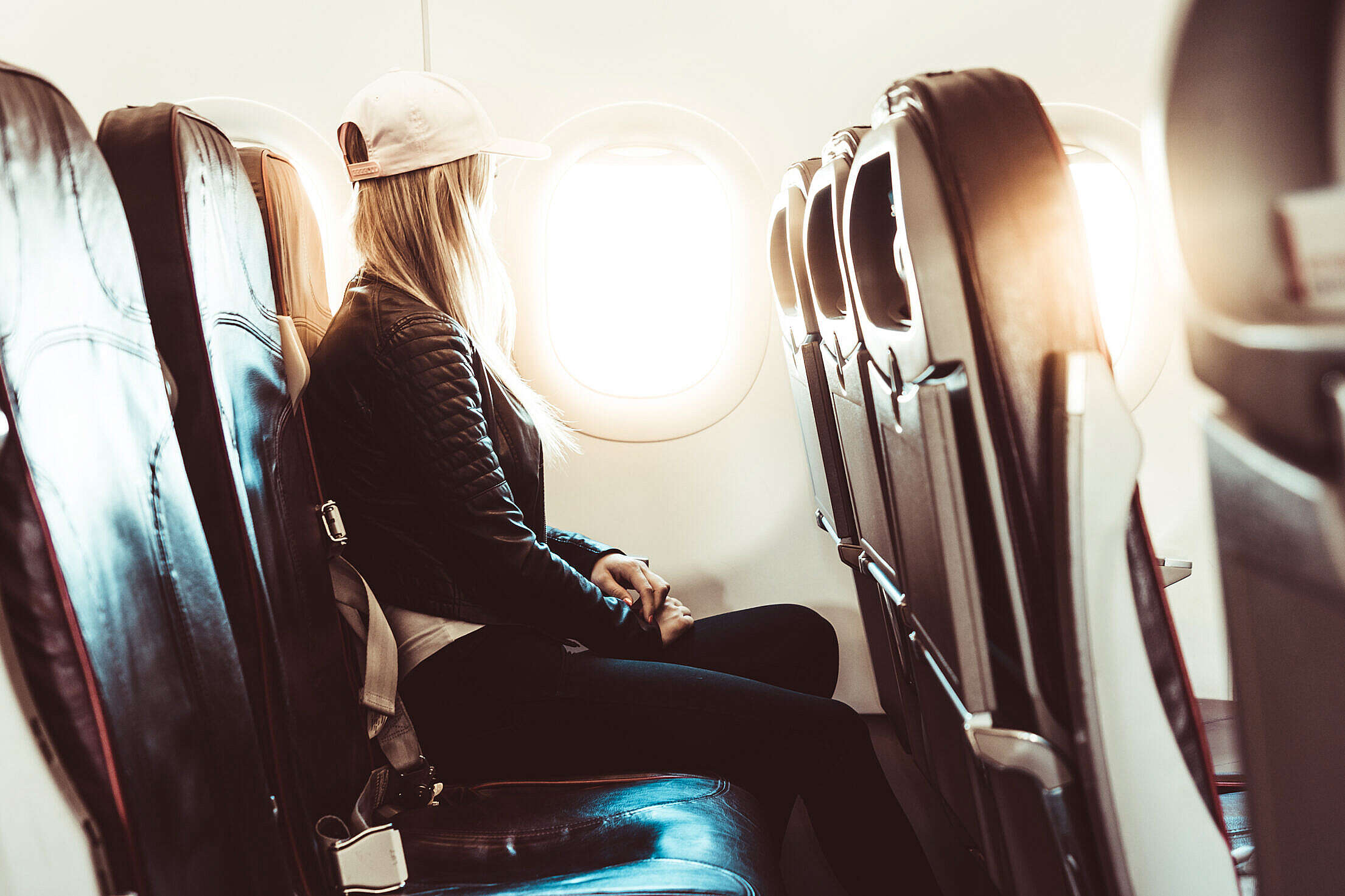 Young Woman Traveling by Airplane Free Stock Photo
