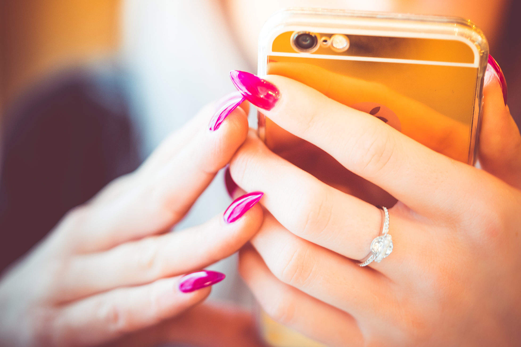 Young Woman Using Her Gold Smartphone Free Stock Photo