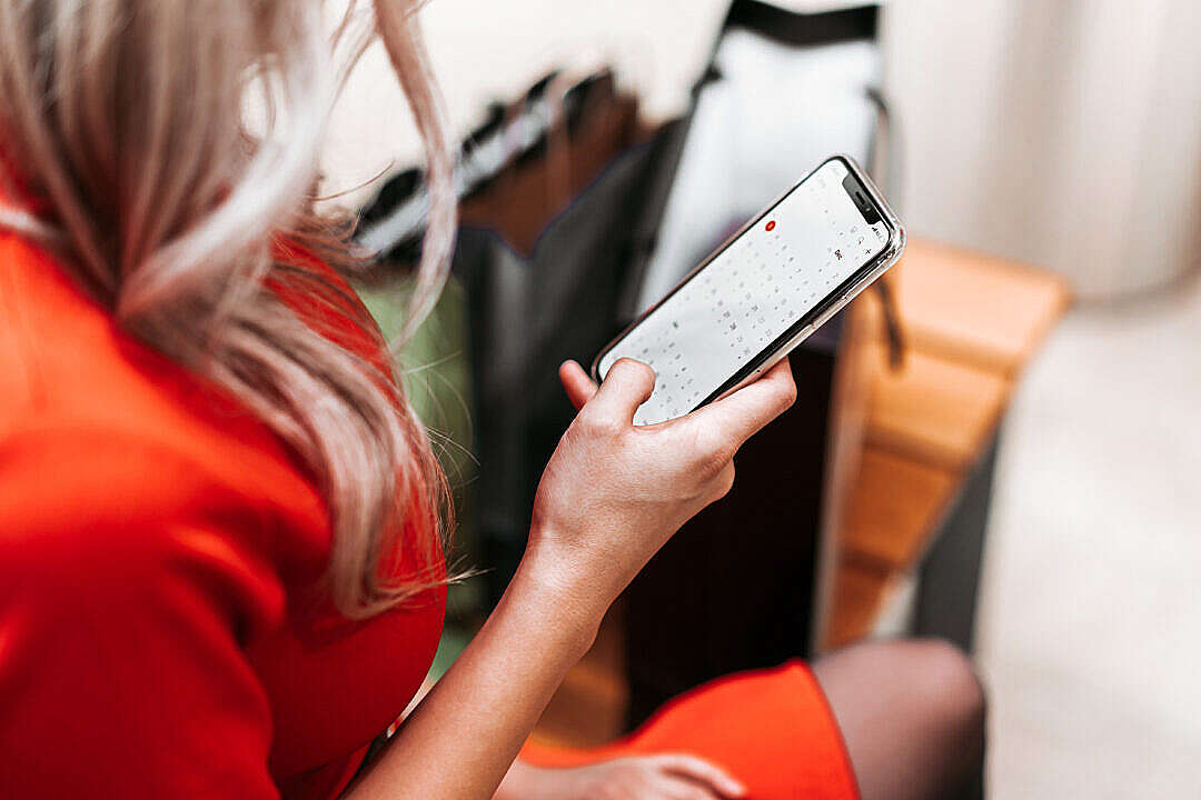 Download Young Woman Using Her iPhone While Shopping FREE Stock Photo