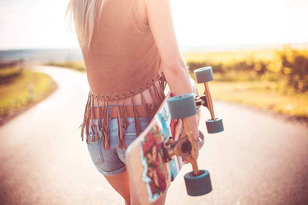 Download Young Woman Walking on The Road and Holding Longboard FREE Stock Photo