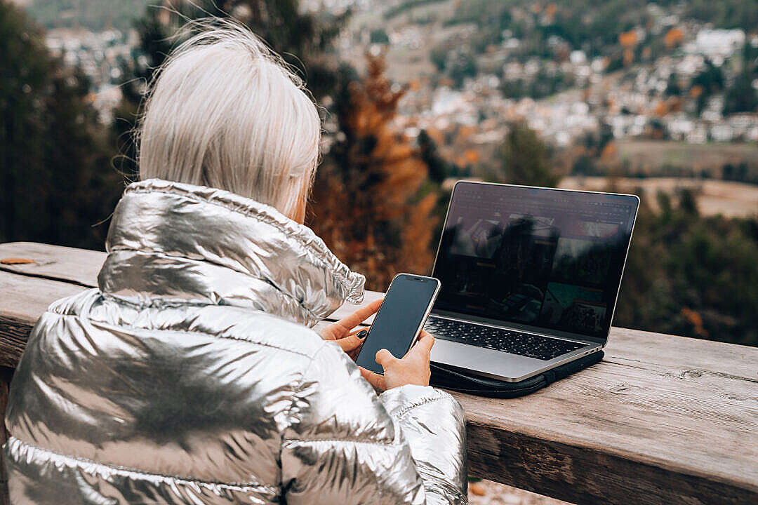 Download Young Woman Working Outdoors on a Laptop and a Mobile FREE Stock Photo