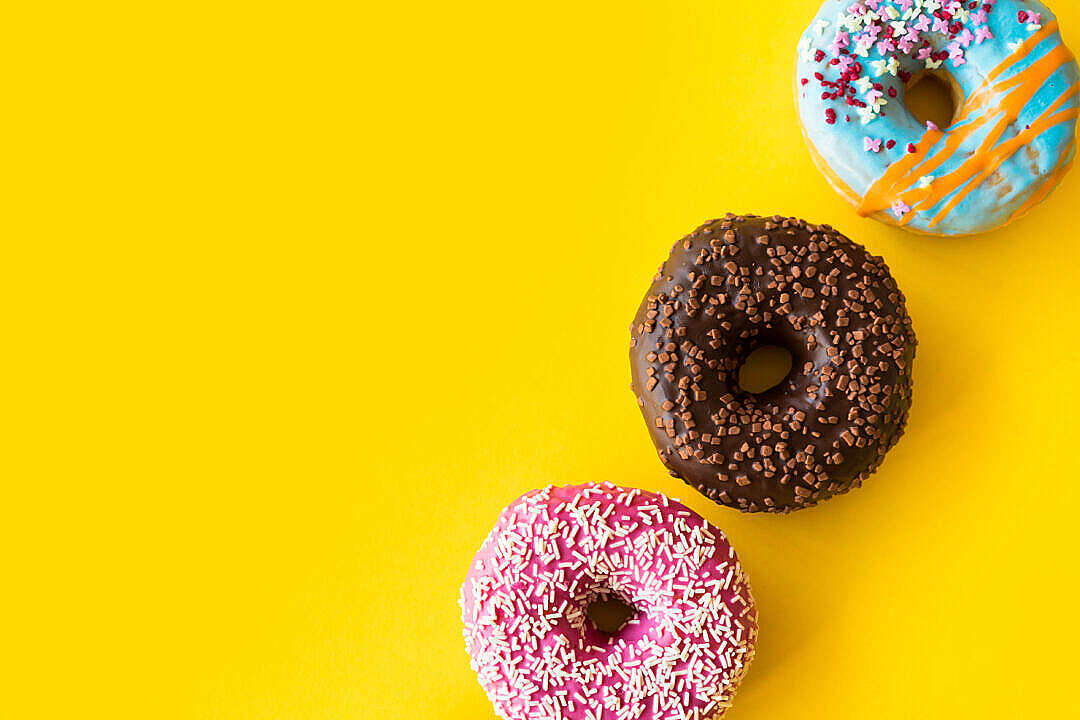 Download Yummy Donuts on Yellow Background FREE Stock Photo