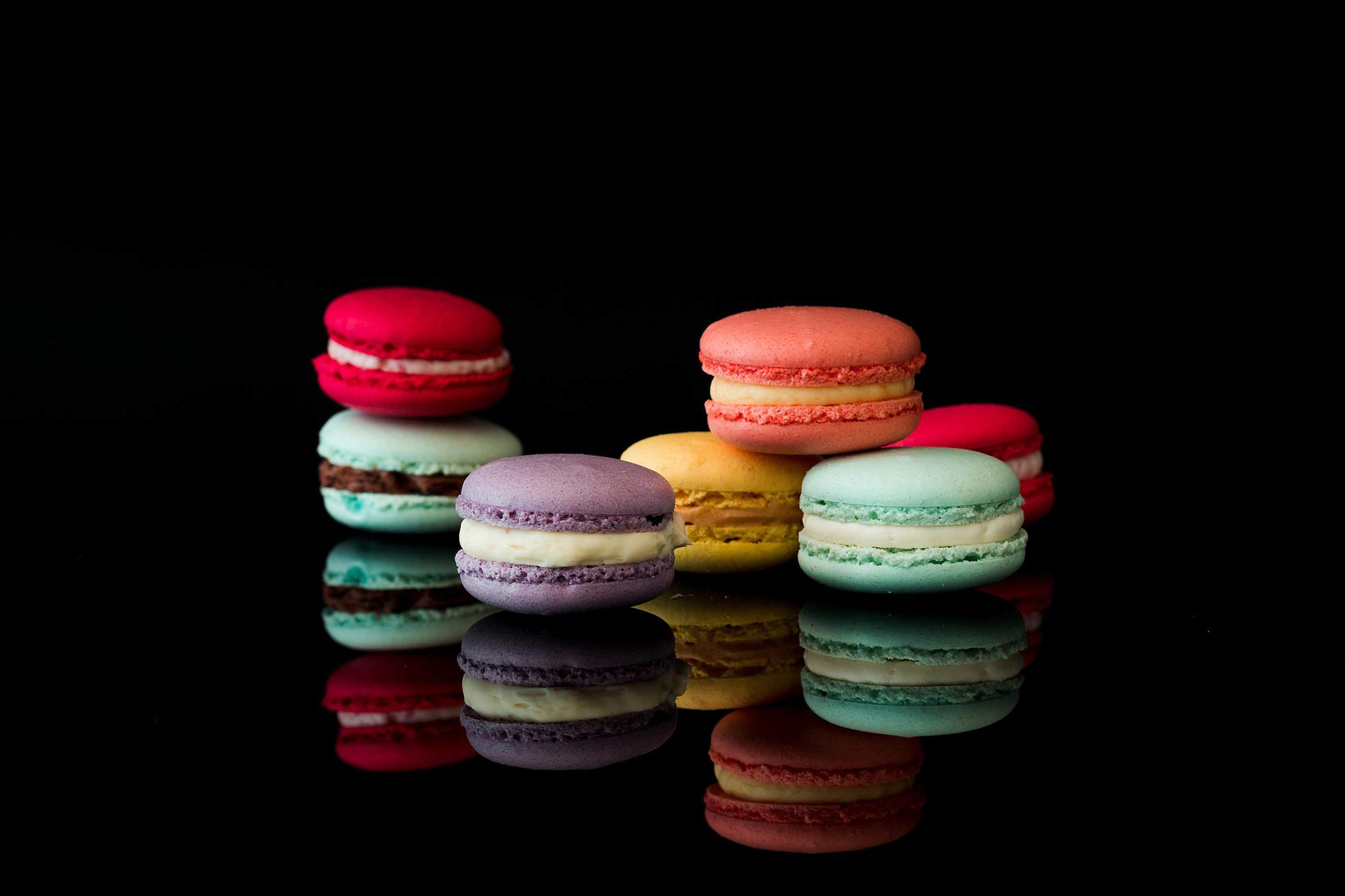 Yummy Macarons on Black Glossy Background Isolated Free Stock Photo